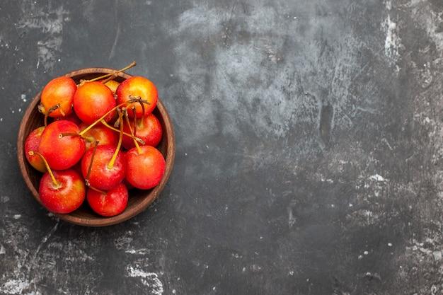 Vers rood kersenfruit in een bruine kom op grijze achtergrond