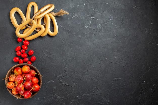 Vers rood kersenfruit in een kom op grijze achtergrond