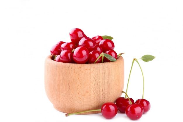 Vers rood kersenfruit in houten kom op wit