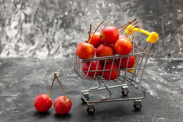 Vers rood kersenfruit in winkelwagen op grijze achtergrond