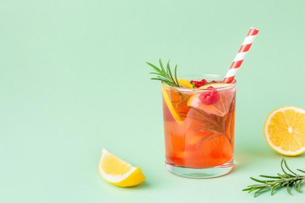 Vers rood water met citroen en framboos en rozemarijn op groene achtergrond. exotische zomerdrank met plakjes citrus met kopieerruimte.