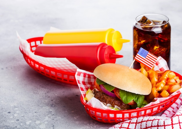 Vers rundvlees hamburger met saus en groenten en glas cola frisdrank met chips frietjes in rode portie mand op stenen keuken.
