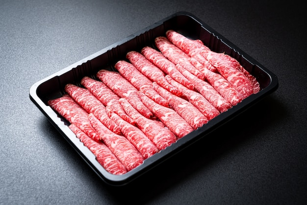 Vers rundvlees rauw gesneden met gemarmerde textuur geserveerd voor sukiyaki en shabu of yakiniku
