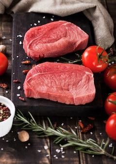 Vers ruw rundvleeslapje vlees op houten keukenraad met tomaten en peper