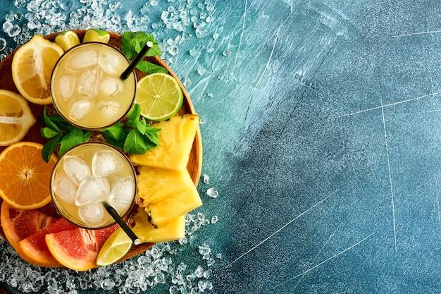 Vers sap ananas met ijs en variëteit gesneden rijp van kleur tropisch fruit grapefruit, sinaasappel, limoen, citroen, plat lag samenstelling, op donkerblauwe stenen achtergrond.