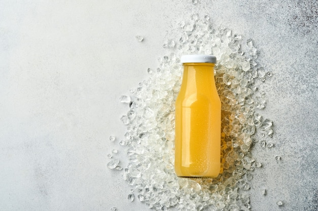 Vers sap ananas op glazen pot met ijs en variëteit gesneden rijp van kleur tropisch fruit grapefruit, sinaasappel, limoen, citroen, plat lag samenstelling, op lichtgrijze stenen achtergrond.