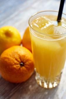 Vers sap in een glas met ijs op tafel en sinaasappels