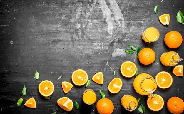 Vers sap van sinaasappels met bladeren.op een zwart bord.
