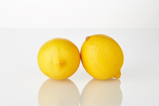 Vers, sappig geel citroenenfruit dat op de witte achtergrond wordt geïsoleerd.