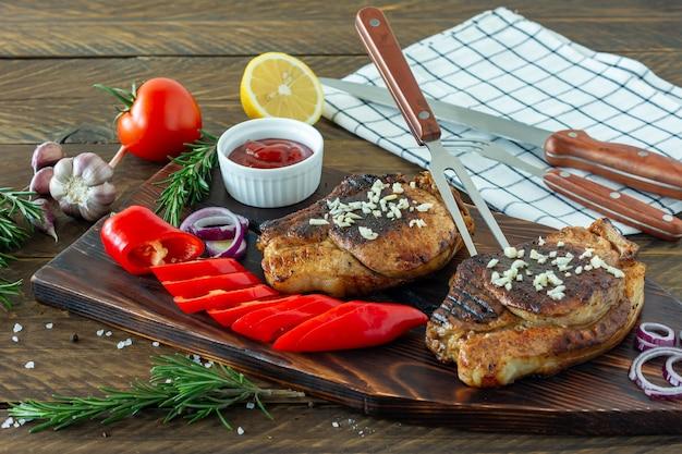 Vers, sappig geroosterd rood vlees op een houten bord, met kruiden en groenten. restaurant eten, heerlijk gerecht.