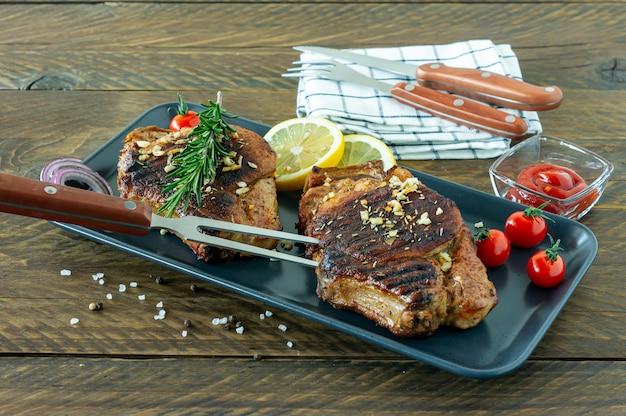 Vers, sappig geroosterd rood vlees op keramische plaat op houten bord, met kruiden en groenten. restaurant eten, heerlijk gerecht.