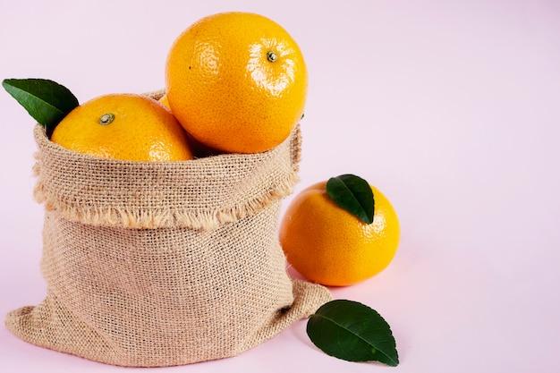 Vers sappig oranje fruit dat over lichtrose wordt geplaatst
