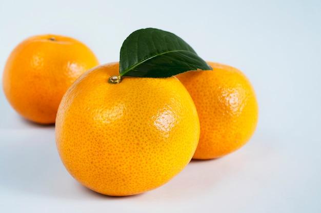 Vers sappig oranje fruit dat over wit wordt geplaatst