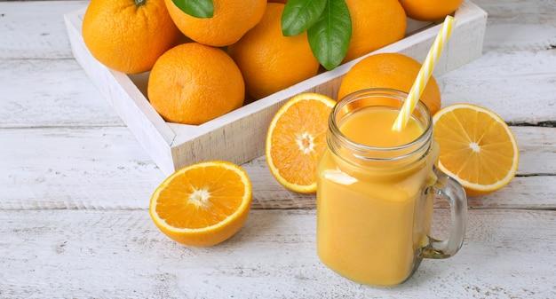 Vers sinaasappelsap in een pot en sinaasappelen op een witte houten tafel in een lade, gezonde voeding