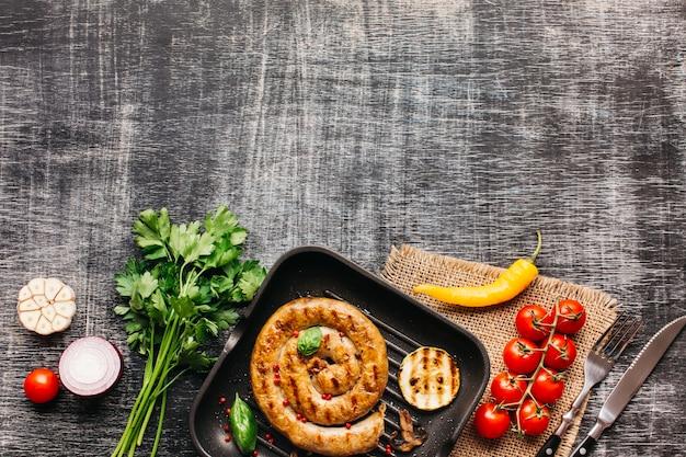 Vers smakelijk ingrediënt en gebraden slakworsten bij bodem van grijze houten geweven