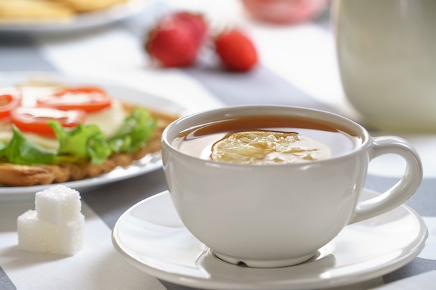 Vers, smakelijk ontbijt met een sandwich en thee op een lichte achtergrond.