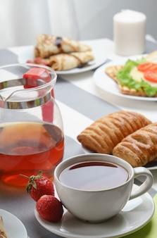 Vers, smakelijk ontbijt met thee en broodjes op een lichte achtergrond.