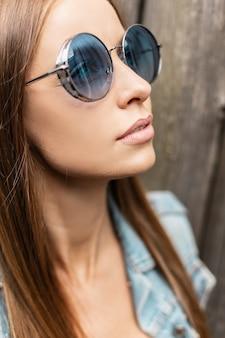 Vers stijlvol portret van mooie jonge vrouw met modieuze ronde blauwe zonnebril in spijkerjasje, close-up