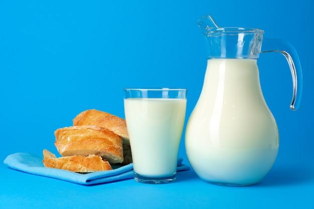 Vers stokbroodbrood en werper met verse melk op blauwe dichte omhooggaand