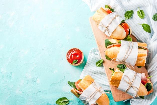 Vers stokbroodsandwich met bacon, kaas, tomaten en spinazie, lichtblauwe copyspace hoogste viewwiches