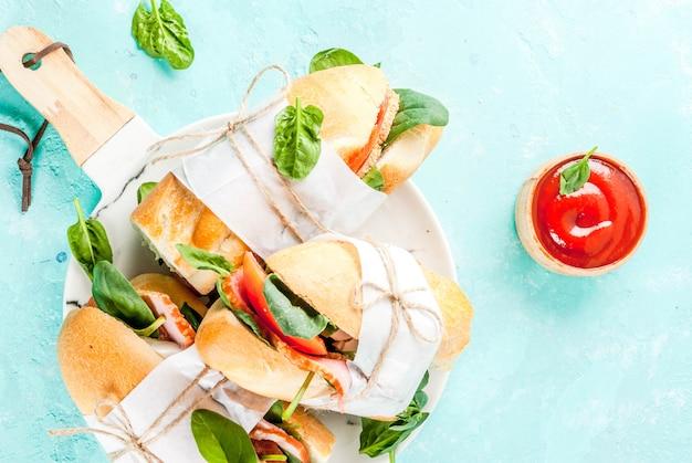 Vers stokbroodsandwich met de tomaten van de baconkaas en spinazie lichtblauwe achtergrond