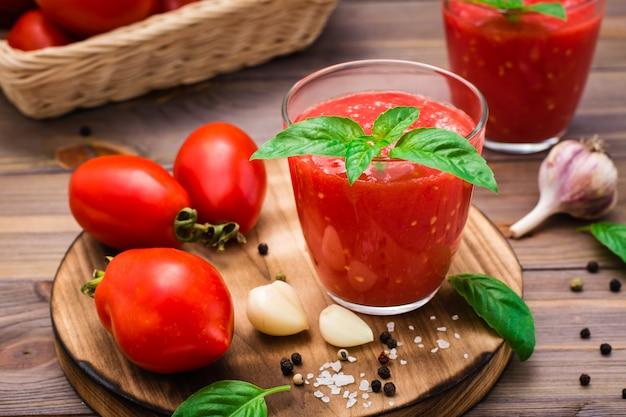 Vers tomatesap met basilicumbladeren in glazen en tomaten op een houten lijst