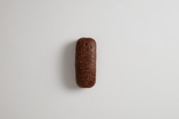 Vers traditioneel geheel donker brood van roggebrood met komijn dat op witte oppervlakte wordt geïsoleerd. volkoren gezonde maaltijd. biologische producten eten. selectieve aandacht. van bovenaf geschoten. voedsel en bakkerijconcept