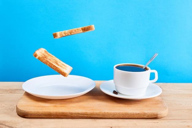 Vers traditioneel ontbijt met knapperige toast en kopje koffie of thee op blauwe achtergrond. levitatie voedselconcept.