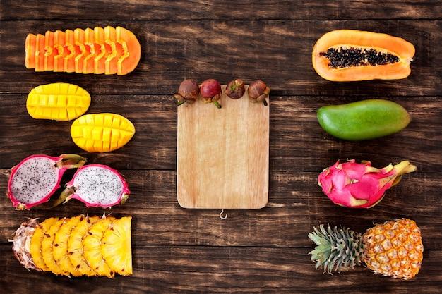 Vers tropisch fruit op donkere houten ondergrond, bovenaanzicht, met wit bord in het midden, kopieer ruimte