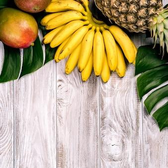 Vers tropisch fruit op hout bovenaanzicht. bananen, ananas, kokos, mango, lychee, kastanjes.