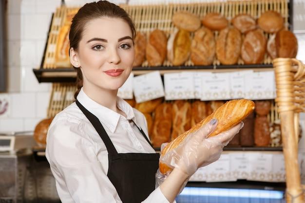 Vers uit de oven. schitterende bakkersvrouw met vers gebakken brood lachend