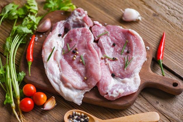 Vers varkensvlees / rauw varkensvlees rozemarijn op witte plaat met kruiden en specerijen tomatengroenten