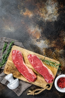 Vers vlees, gemarmerd rundvlees, biefstuk van rauwe reepjes. donkere achtergrond. ruimte voor tekst. plat liggen.