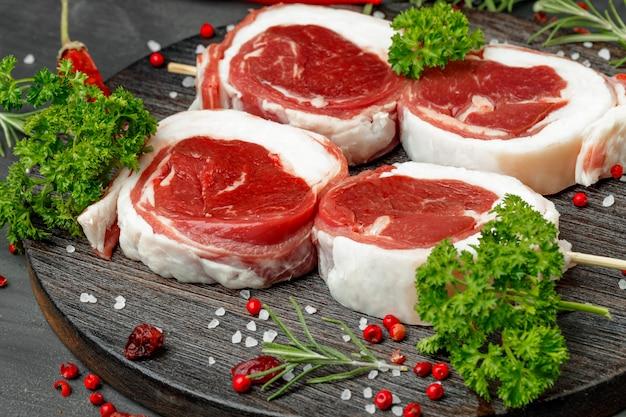 Vers vlees met ingrediënten voor het koken op een donkere achtergrond