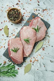 Vers vlees met kruiden op een lichte achtergrond. gesneden verse steaks. ruimte voor tekst.
