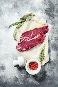 Vers vlees, vacuüm verpakt gemarmerd rundvlees, biefstuk van de lendenen. donkere achtergrond. ruimte voor tekst. verpakkingen van supermarkt