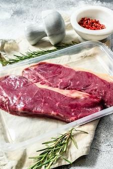 Vers vlees, vacuüm verpakt gemarmerd rundvlees, biefstuk van de lendenen. donkere muur. verpakkingen van supermarkt.