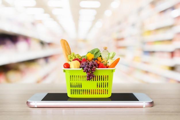 Vers voedsel en groenten in winkelmandje op mobiele smartphone op houten tafel met supermarkt gangpad wazig achtergrond kruidenier online concept