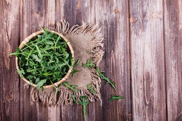 Vers voedsel, gezond leven. groene rucola diende in de kom op rustieke achtergrond