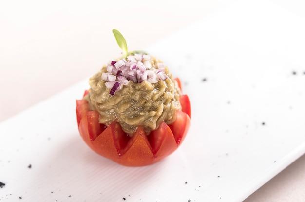 Vers voorgerecht met auberginesalade, geplaatst in een tomatenmand, versierd met ui en