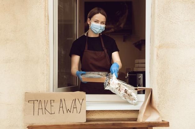 Vers. vrouw die drankjes en maaltijden bereidt, een beschermend gezichtsmasker en handschoenen draagt. contactloze bezorgservice tijdens quarantaine coronavirus pandemie. afhaalconcept. recyclebare mokken, pakketten.