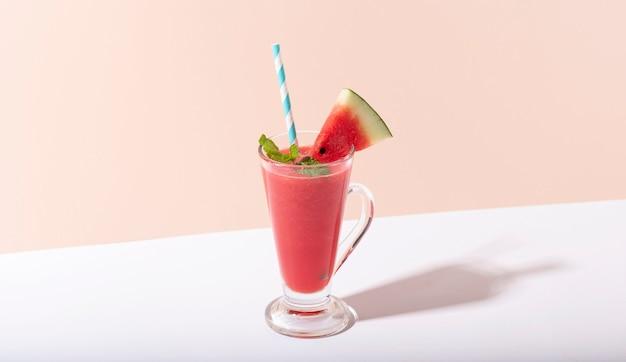 Vers watermeloensap en watermeloenplak op kleurenachtergrond. zomer drankje.