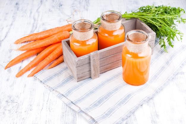 Vers wortelsap in een kruik. verse wortelen met bladeren en drinken. lente voedsel voor gezondheid en schoonheid