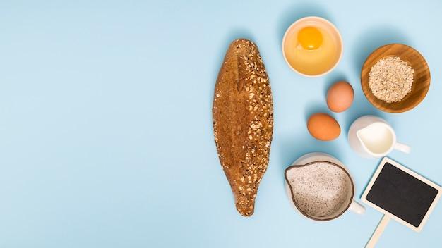 Vers zelfgebakken brood; ei; haver schuur; melk; meel en aanplakbiljet op blauwe achtergrond