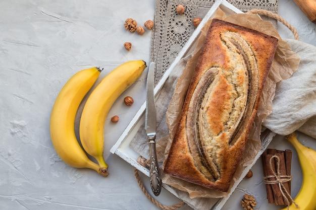 Vers zelfgemaakt bananenbrood in wit houten dienblad met ingrediënten op lichte betonnen ondergrond