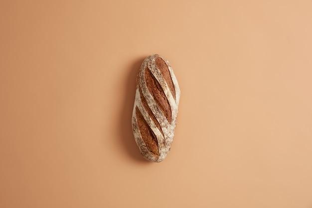 Vers zelfgemaakt knapperig frans volkorenbrood bereid van biologische bloem, gemaakt op zuurdesem, geïsoleerd op bruine studioachtergrond. bakkerij en voedselconcept. thuis koken en eten bereiden.