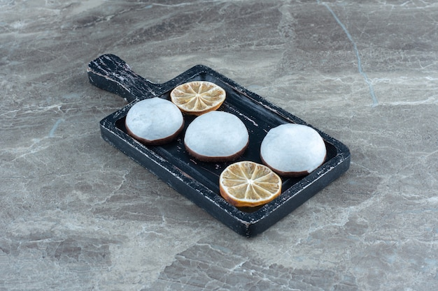 Vers zelfgemaakt koekje met droge schijfje citroen op een houten bord.