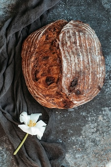 Vers zuurdesembrood op zwarte achtergrond. vers gebakken zelfgemaakt roggebrood, bovenaanzicht. brood met noten en gekonfijt fruit.