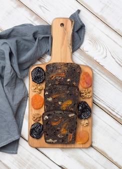 Vers zwart dessertbrood met gedroogde pruimen, gedroogde abrikozen en walnoten op houten achtergrond.