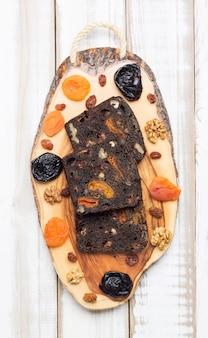 Vers zwart dessertbrood met pruimen, gedroogde abrikozen en walnoten.